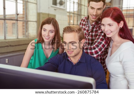 Smiling group of young people in the office clustered around a young man at a desktop computer reading the information on the screen - stock photo