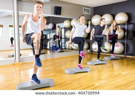 Smiling group raising legs on step platforms at fitness gym - stock photo