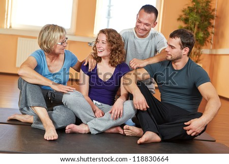 Smiling group with men and women talking in a fitness center
