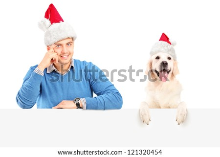 Smiling guy and dog wearing santa claus hats and posing behind a blank panel - stock photo
