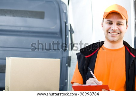 Smiling guy delivering a parcel - stock photo