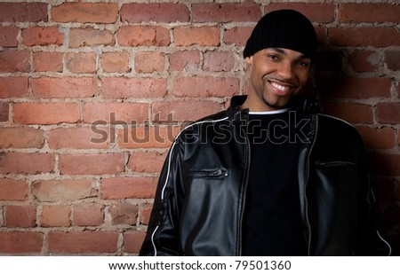 Smiling guy dressed in black near a brick wall. - stock photo