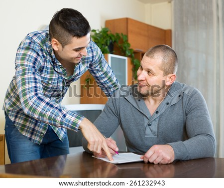 Smiling guy explains to his friend to fill banking document at home