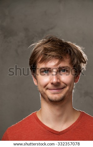 Smiling guy in the red shirt on a gray background.