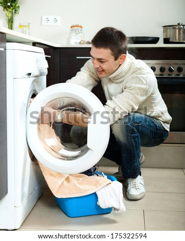 Smiling  guy looking  clothes near washing machine