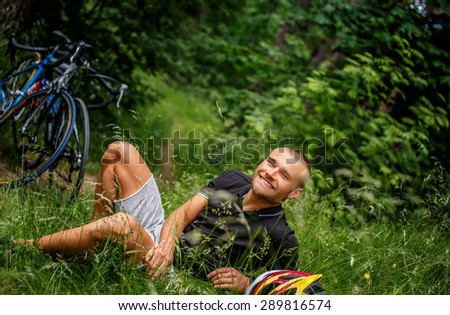 Smiling guy lying on grass. Cycles on background.