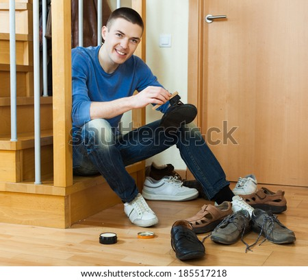 Smiling guy sitting on stairs and cleaning footwear