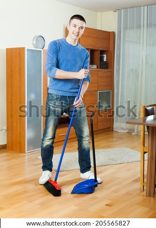 Smiling guy  sweeping the floor in living room at home