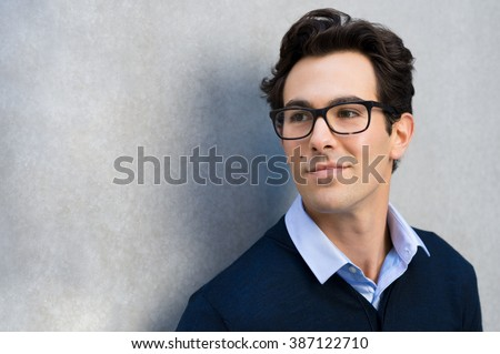 Smiling guy wearing glasses looking away and leaning on grey wall. Portrait of young businessman with eyeglasses thinking about his carrer with copy space.