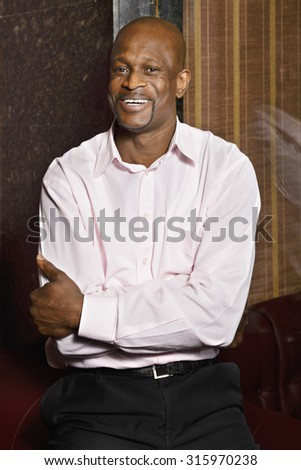 Smiling guy wearing pink shirt at glass wall arms folded - stock photo
