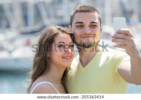 Smiling guy with girlfriend doing selfie during city tour at vacation