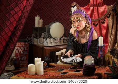 Smiling gypsy soothsayer with hand of tarot cards - stock photo
