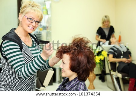 Smiling hairdresser makes hair styling for woman by rake-comb and looks at camera in beauty salon; focus on barber; other barber washes second client head - stock photo