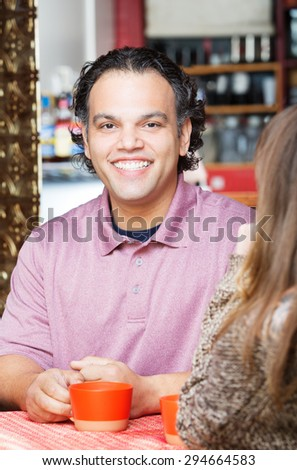 Smiling handsome African American man having coffee with friend