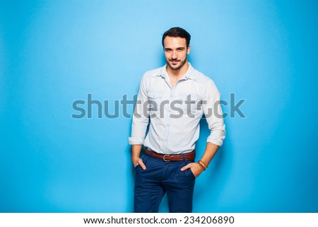 smiling handsome and masculine man in blue pants and jeans shirt on a blue background - stock photo