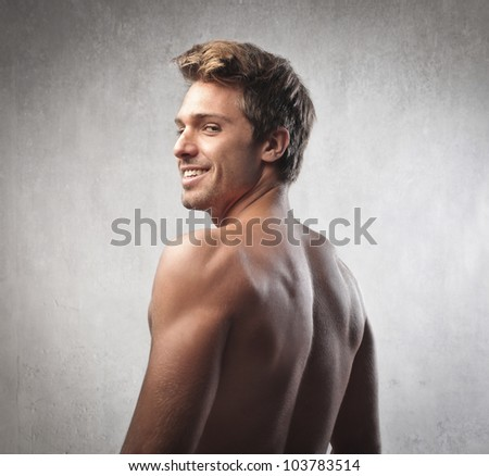 Smiling handsome brawny young man - stock photo