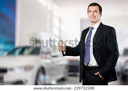 Smiling handsome business man car dealer showing thumb up - stock photo
