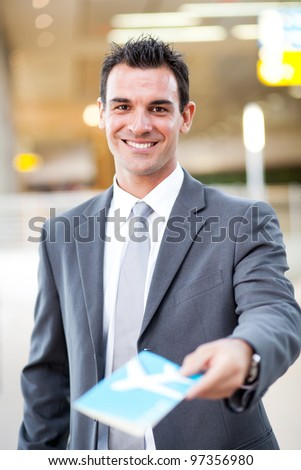smiling handsome businessman handing over air ticket at airport check in counter - stock photo