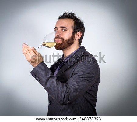 Smiling handsome businessman holding a glass of wine