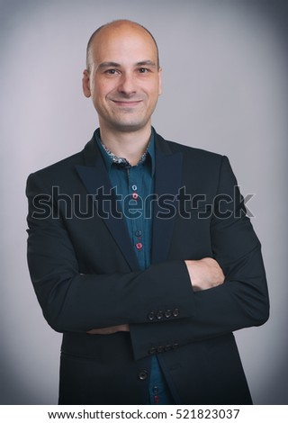 smiling handsome businessman in suit with his arms folded