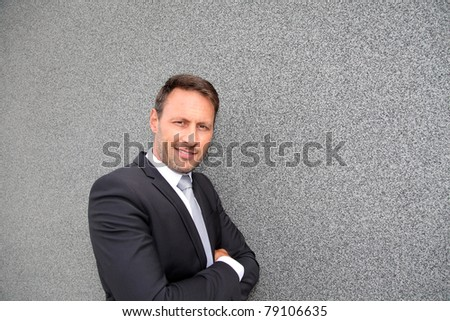 Smiling handsome businessman leaning on concrete wall - stock photo