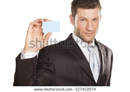 smiling handsome businessman showing a credit card - stock photo