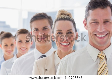 Smiling handsome businessman standing with his team in the office