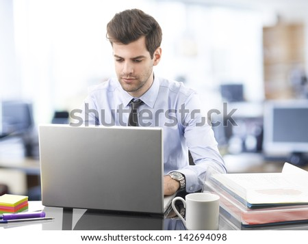 Smiling handsome businessman using laptop in office - stock photo