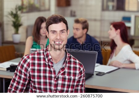 Smiling handsome casual young businessman in a checked shirt posing in front of a group of his colleagues who are deep in discussion - stock photo