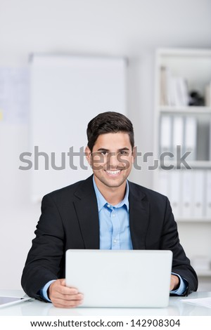 Smiling handsome caucasian businessman sitting at the desk with a laptop computer in the office