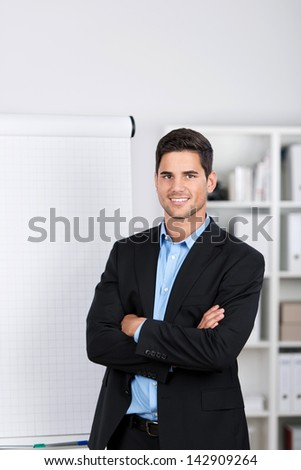 Smiling handsome caucasian businessman standing by the side of a blank flip-chart in the office - stock photo