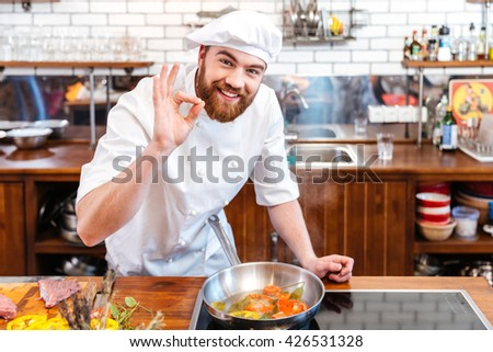 Smiling handsome chef cook preparing food and showing ok gesture on the kitchen - stock photo