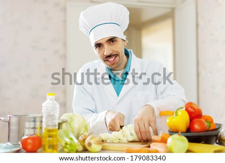 Smiling handsome cook does vegetarian lunch at kitchen - stock photo