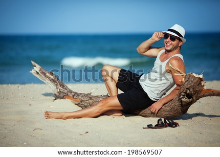 Smiling handsome guy in sunglasses sitting on sand beach