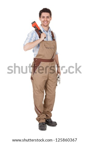 Smiling handsome handyman in work clothes with tool