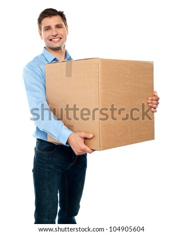 Smiling handsome male carrying box moving into new office