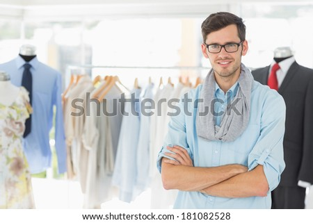 Smiling handsome male fashion designer with arms crossed in the studio - stock photo