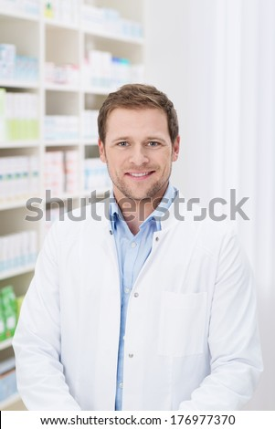 Smiling handsome male pharmacist standing in the pharmacy in his white coat - stock photo