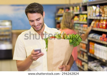 Smiling handsome man buying food products and using his smartphone at supermarket - stock photo