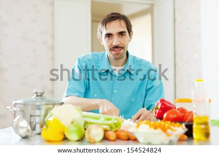 Smiling handsome  man cooking  vegetables - stock photo