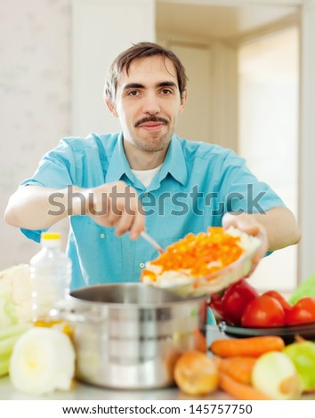 Smiling handsome man cooks lunch with vegetables - stock photo