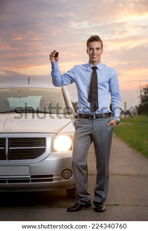 Smiling handsome man holding keys of new car - stock photo