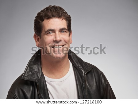 Smiling handsome man in black leather jacket - stock photo