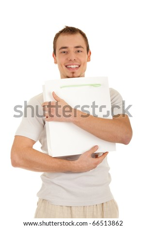 Smiling handsome man is embracing white gift paper bag. Isolated on white background.