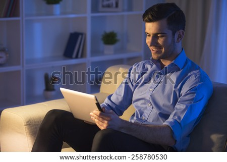 Smiling handsome man is using digital tablet at home. Side view. - stock photo
