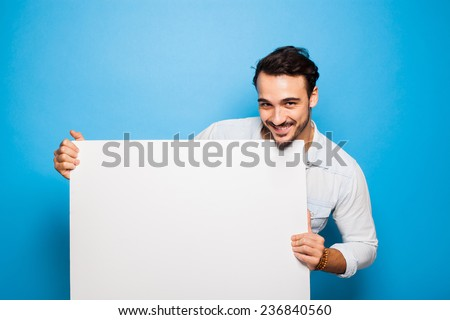 smiling handsome man looking into camera and holding a blank panel on blue background - stock photo