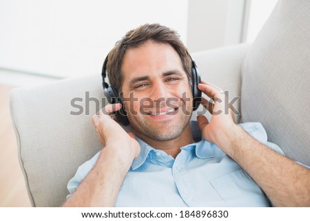Smiling handsome man lying on sofa listening to music looking at camera at home in the living room