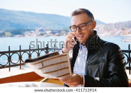 Smiling handsome man phoning and holding newspaper at cafe near the sea - stock photo