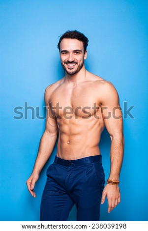smiling handsome man shirtless and sexy on blue background
