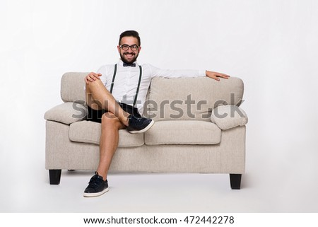 Smiling handsome man sitting on couch or sofa and looking at camera. Young man in shirt and shorts posing isolated on white background. Emotions concept.